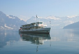 Boat on a Swiss lake with Alps mountains