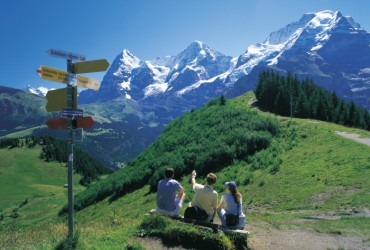 Guidepost on the Allmendhubel trail (1399 m) above Muerren in the Bernese Oberland. Panoramic vista of the Eiger, Moench and Jungfrau.