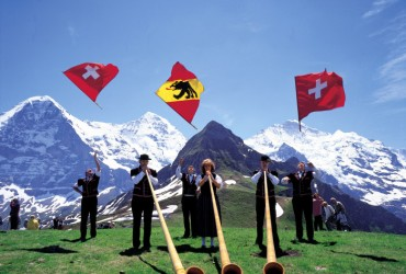 The Maennlichen (2343 m) located in the Bernese Oberland. Eiger, Moench, Tschuggen and Jungfrau form a majestic backdrop for alphorn blowers and flag swingers.