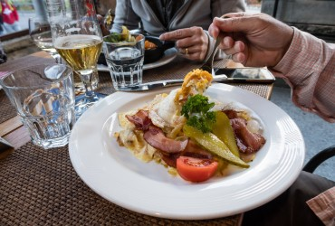 A fancy rösti or röschti dinner plate can be heaped with potatoes, egg, bacon, tomato and pickles.